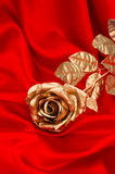 Golden rose flower over smooth red satin Royalty Free Stock Photos