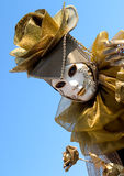 Golden rose and a white mask. A person in a golden Venice carnival costume with a white mask Royalty Free Stock Photos