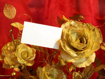 Golden roses and postcard. On red background Royalty Free Stock Images