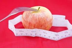 Golden-roter Apfel mit einem Messinstrument und eine Gabel auf Rot Stockbild