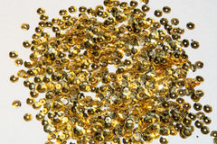 Golden round sequins sewing on white background Stock Photography
