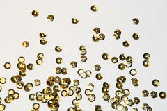 Golden round sequins sewing on white background Royalty Free Stock Photo
