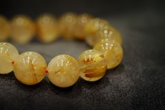 Golden Rutilated Quartz  Bead bracelets lucky gemstone supplement good fortune. With black background stock images