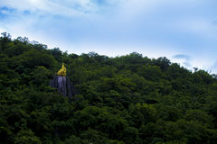 Golden sacred rock at Wat Thewarup Song Tham, Thailand surrounded by forest under the blue sky. Royalty Free Stock Photo