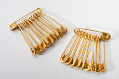 Golden safety pin on a white background Stock Photo