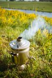 Golden samovar on the nature of the river smokes and heats water royalty free stock image