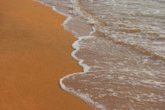 Golden Sand Background with wave, tropical lagoon resort, a lot of space for text Royalty Free Stock Photo