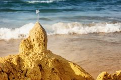 Golden sand castle background with copy space. Sand castle with white flag on top built by the child at the water's edge. Castle is made of golden sand royalty free stock photography