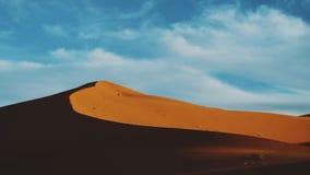 Golden sand and cloudy sky in Sahara desert. Sunset. Beautiful desert landscape. Sahara desert. Sand dunes Arabian