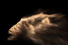 Golden sand explosion isolated on black background. Abstract sand cloud. Golden colored sand splash against dark background. Yellow sand fly wave in the air stock images