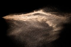 Golden sand explosion isolated on black background. Abstract sand cloud. Golden colored sand splash against dark background. Yellow sand fly wave in the air stock photography