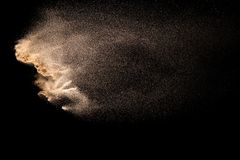 Golden sand explosion isolated on black background. Abstract sand cloud. Golden colored sand splash against dark background. Yellow sand fly wave in the air stock photo