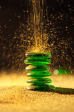 Golden sand falling on balancing green stones. Golden sand falling on green glass stones,shallow DOF stock image