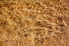 Free Golden Sand Under Clear Sea Water And Sunlight Glow Reflection Close Up Top View, Yellow Sandy Texture Below Ocean Water Royalty Free Stock Image - 161671866