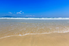 Golden sand and wave beach blue sky daylight landscape Royalty Free Stock Photography