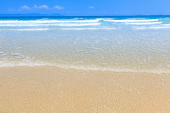Golden sand and wave beach blue sky daylight landscape Royalty Free Stock Image