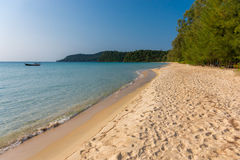 Golden sandy beach of tropical island with forested headland. In the distance and clam turquoise sea Stock Photos