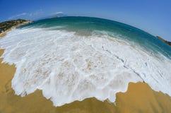 Golden sandy beach with white waves Stock Photos