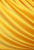 Golden satin, silk waves. Yellow background Stock Photos