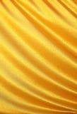 Golden satin, silk waves. Yellow background Stock Photos