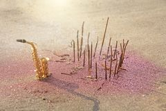The golden saxophone alto stands on the sand next to the fragrant and pink shining. Romantic musical background. Musical cover,. Creative, relaxation and stock photo