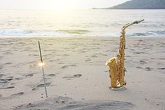 The golden saxophone alto stands on the sand and on the shore, against the background of the sea and Bengal lights. Romantic stock photography