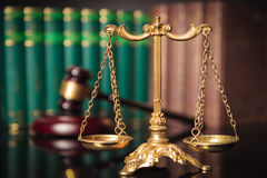 Golden scale in front of judge's gavel and law books Royalty Free Stock Images
