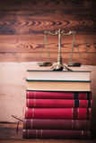 Golden scale on top of stack of law books. Against old wooden background Royalty Free Stock Image
