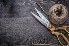 Golden scissors skein of rope on vintage wooden board Stock Photography
