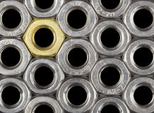 Golden screw nut. In steel nuts pattern  on black Stock Photos