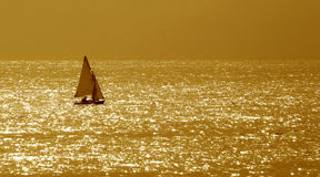 Golden Sea. Small boat on the golden surface of Mediterranean sea Royalty Free Stock Photography