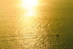 Golden sea with moving boat Stock Photos