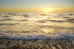 Golden sea sunset with braking waves Stock Photography