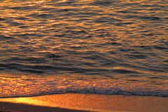 Golden sea waves and sand at sunset. Closeup Royalty Free Stock Photography