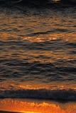 Golden sea waves and sand at sunset. Closeup Stock Photography