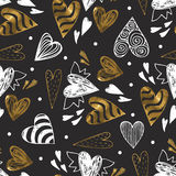 Golden seamless pattern with the image of tribal hearts Royalty Free Stock Image