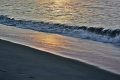 Golden Seas at Sunrise at the Shore. The sunrises over the ocean on a summer morning at the shore producing golden and glowing seas Royalty Free Stock Images