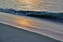 Golden Seas at Sunrise at the Shore. The sunrises over the ocean on a summer morning at the shore producing golden and glowing seas Royalty Free Stock Photography