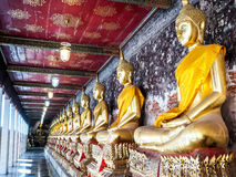 Golden seated Buddha images at corridor. Stock Photo