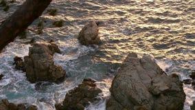 Golden Seawater on the Rocks stock video