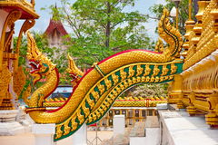 Golden serpent or naga on staircase. To pagoda in Thai temple beside view Royalty Free Stock Image