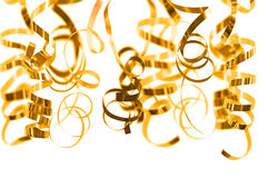 Golden serpentine streamers hanging on white. Background stock photography