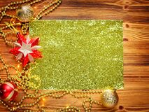 Golden sheet of paper surrounded by Christmas decorations gold and red balloons on a wooden background. There is space for text