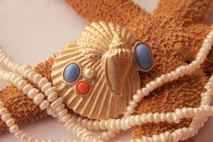 Golden shell with pearl, turquoise, coral, starfis Royalty Free Stock Images