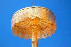 Golden shield against a blue sky Stock Photos