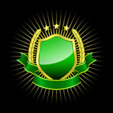 Golden shield with green ribbon Royalty Free Stock Image