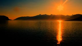 Golden shimmering over the fjord with mountains in the back stock photography