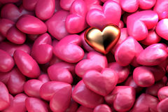 Golden shining heart on a background of pink shiny hearts. Beautiful festive backdrop for Valentine`s day. Stock Photos