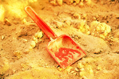 Golden shining sand and plastic sovochke. Symbol of gold mining. The gold-bearing rock. Also a symbol of a happy golden childhood and bright precious memories Stock Photos