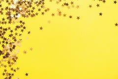 Golden shining stars confetti on yellow. Golden shining stars on yellow background. Party Happy Birthday Anniversary Background. Confetti background royalty free stock image